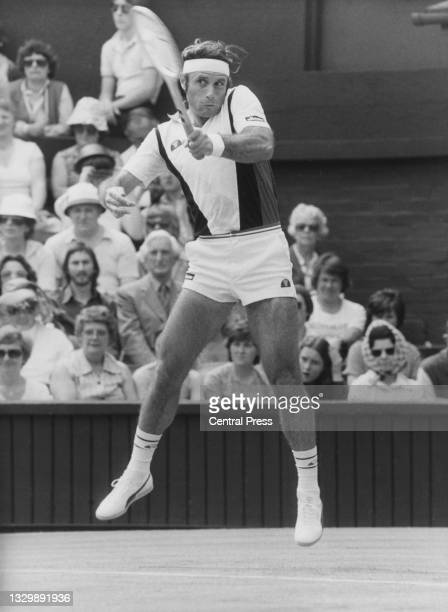 Guillermo Vilas of Argentina jumps to play a forehand return to Mark Edmondson of Australia during their Men's Singles First Round match at the...