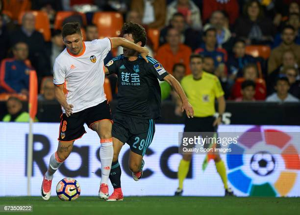 Guillherme Siqueira of Valencia competes for the ball with Alvaro Odriozola of Real Sociedad during the La Liga match between Valencia CF and Real...