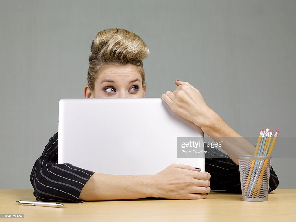 Guilty businesswoman behind laptop : Stock Photo