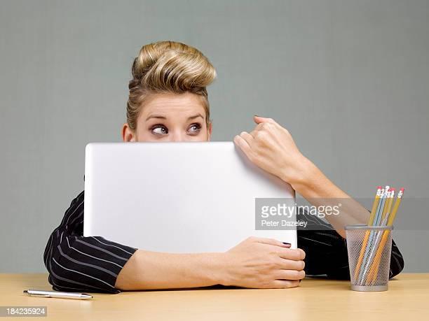 Guilty businesswoman behind laptop