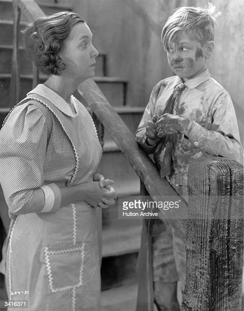 Guilty looking child star Mickey Rooney encountering ZaSu Pitts while covered in mud in a scene from the film 'Love Birds'