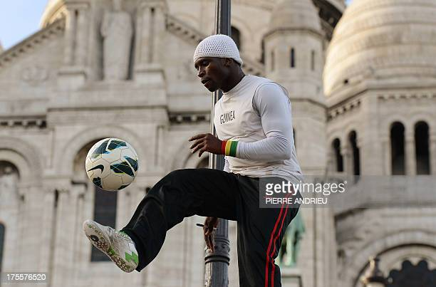 Guinea born Iya Traore a former football player juggler and acrobate performs with a ball in front of the Sacre Coeur basilica in the neighborhood of...
