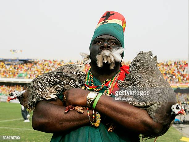 A Guinea fan holding two guinea fowl birds during the opening Group A match of the 2008 African Cup of Nations between Ghana and Guinea in the Ohene...