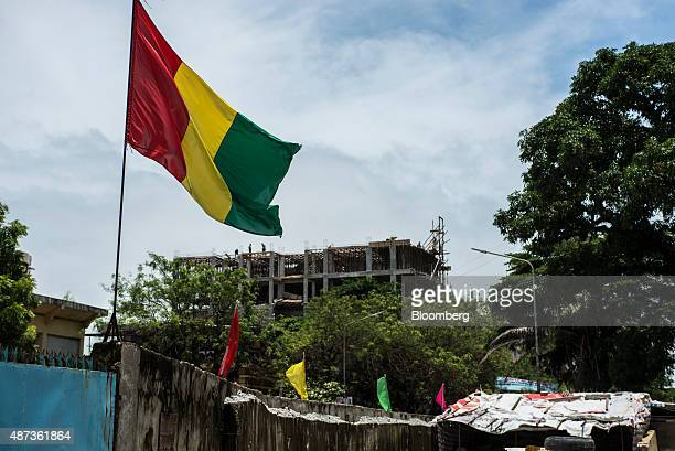 A Guinea national flag flies at the entrance to a Chinese construction site in Conakry Guinea on Saturday Sept 5 2015 While Guinea produces bauxite...