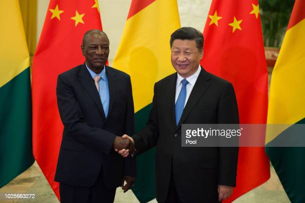 Guinea President Alpha Conde shake hands with China's President Xi Jinping before their bilateral meeting at the Great Hall of the People in Beijing...