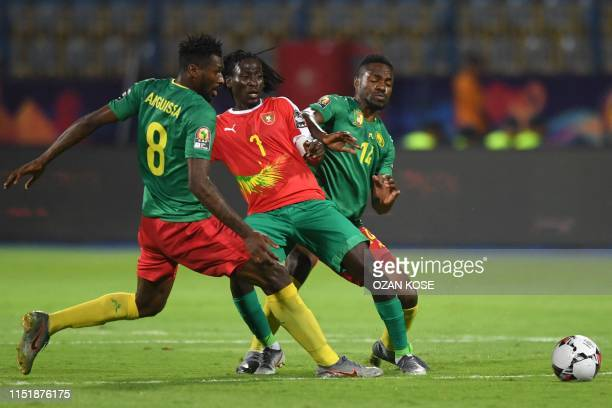 GuineaBissau's midfielder Zezinho Lopes passes the ball as he is closed down by Cameroon's midfielder AndreFrank Zambo Anguissa and GuineaBissau's...