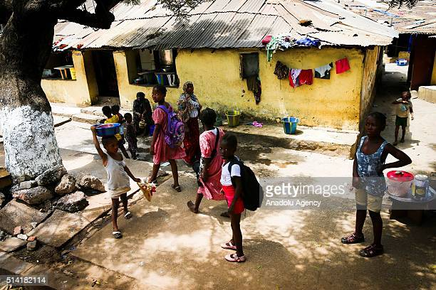 Guinean children walk towards a school in Conakry Guinea on March 7 2016 Guinean women give their children to foreigners who visit their country...