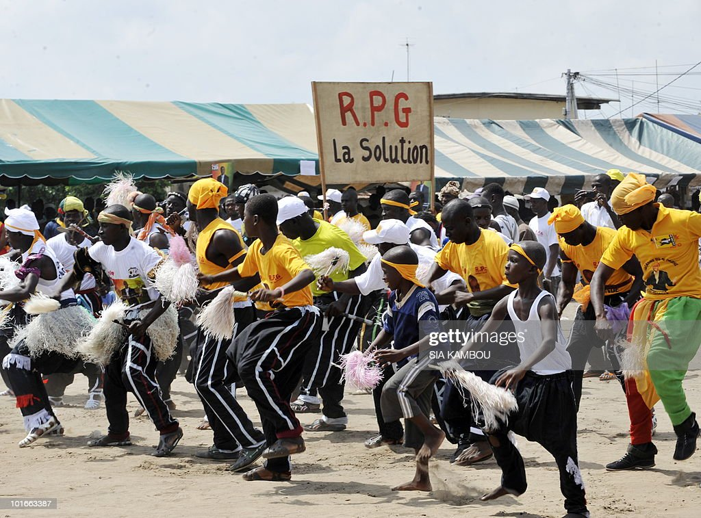 Guinean dancers with a banner saying ' RPG the solution ' and supporters of the RPG political party of Guinean opposition leader Alpha Conde, in Koumassi, a popular area of Abidjan on June 6, 2010, during a political gathering of Guineans living in Ivory coast to show their support to Mr Alpha Conde ahead of the Guinean presidential election on June, 27, 2010.