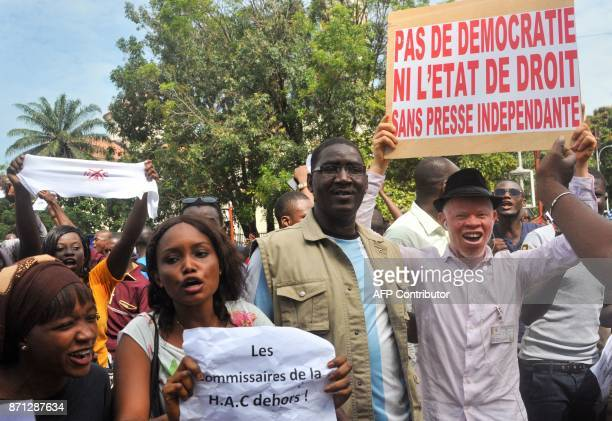 Guinean journalists hold placards reading 'No democracy or rule of law without independent press' and 'Commissioners of the high authority of...