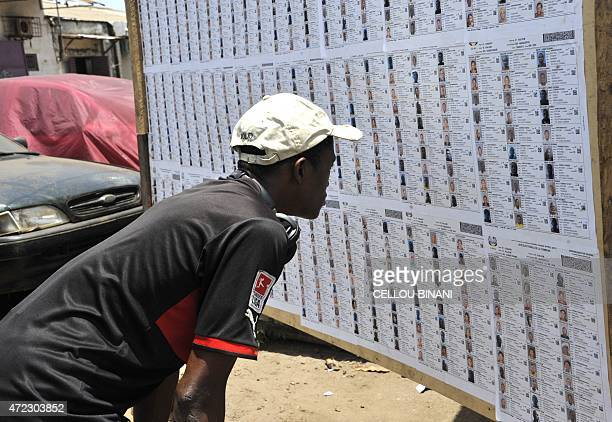 A Guinean man looks at a list of candidates on May 2 2015 made available by the electoral commission and displayed on a board in the capital Conekry...