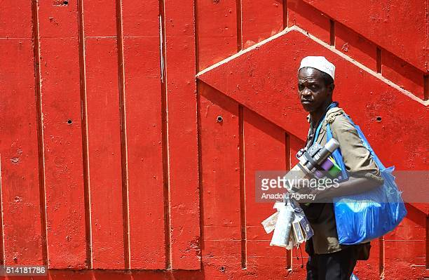 Guinean man tries to sell goods as he walks in Conakry Guinea on March 7 2016 Guinean women give their children to foreigners who visit their country...