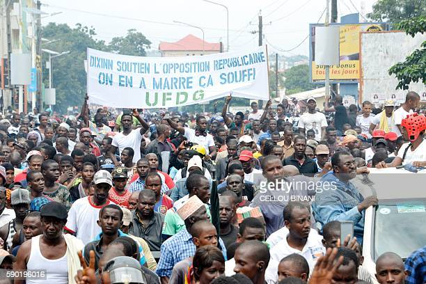 Guinean opposition supporters march with banner reading 'Support to opposition That is enough' during an antigovernment protest in Conakry on August...