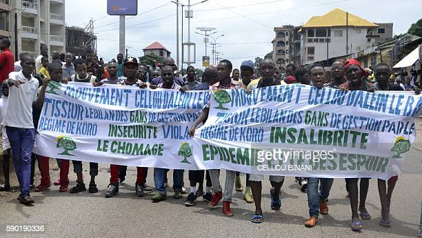 Guinean opposition supporters march with banners during an antigovernment protest in Conakry on August 16 2016 / AFP / CELLOU BINANI