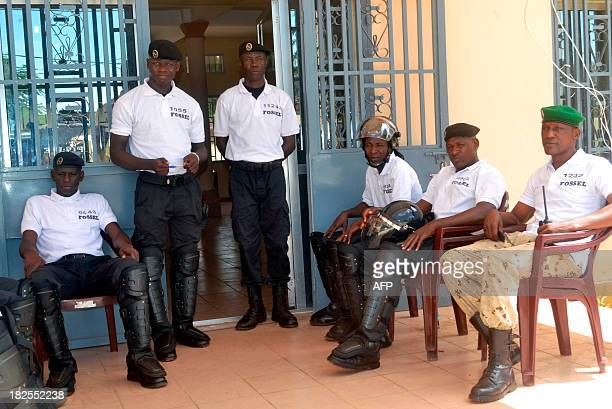 Guinean policemen stand guard in front of a vote counting centre in Matoto in the Conakry region on September 30 two days after the first...