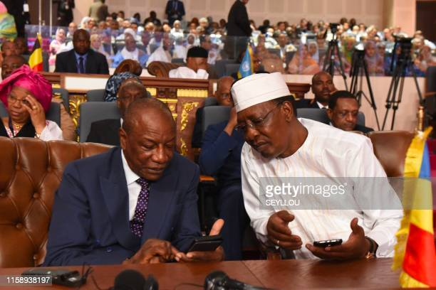 Guinean President and Chairman of the African Union Alpha Conde speaks with Tchadian president Idriss Deby during the newly elected Mauritania's...