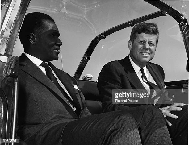 Guinean president Sekou Toure sits and smiles with American president John F Kennedy in the back of Kennedy's custom 'bubbletop' Lincoln Continental...