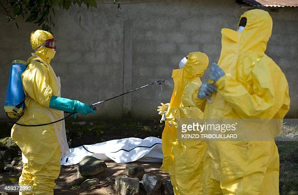 Guinean Red Cross workers prepare to carry the corpse of a victim of Ebola in Macenta on November 21 2014 The World Health Organisation said that...
