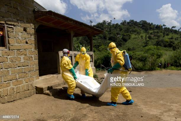 Guinean Red Cross workers wearing protective suits carry the corpse of a victim of Ebola in Macenta on November 21 2014 The World Health Organisation...
