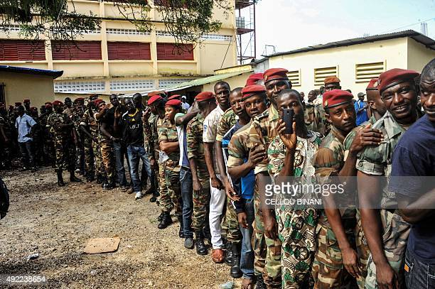 Guinean soldiers queue to cast their ballots at a polling station during the first round of the country's presidential election in Conakry on October...