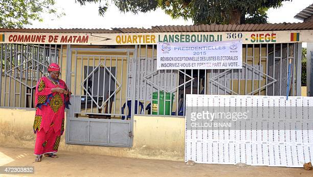 A Guinean woman arrives to consult a list of candidates on May 2 2015 made available by the electoral commission and displayed on a board in the...