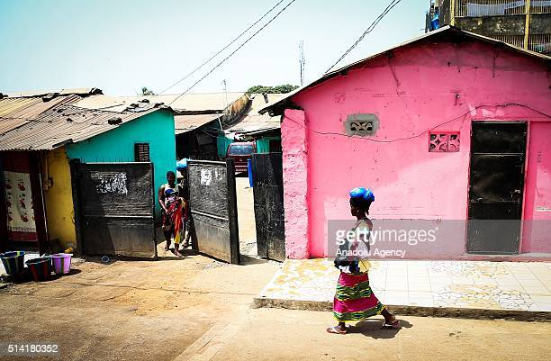 Guinean woman carries plastic bags on her head as she passes by colorful houses in Conakry Guinea on March 7 2016 Guinean women give their children...