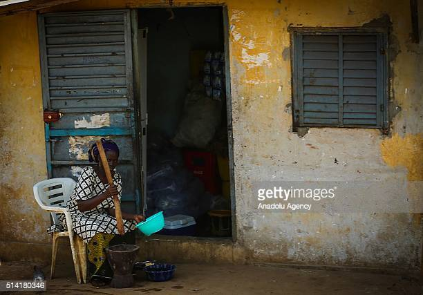 Guinean woman prepares food in front of her house in Conakry Guinea on March 7 2016 Guinean women give their children to foreigners who visit their...