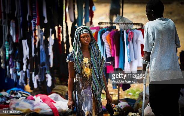 Guinean woman walks at a market place in Conakry Guinea on March 7 2016 Guinean women give their children to foreigners who visit their country...