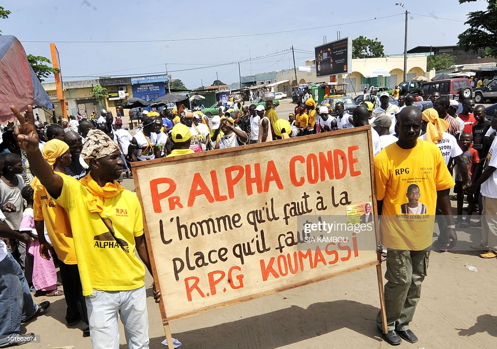 Guineans living in Ivory coast and supporters of Guinean opposition leader Alpha Conde who is the leader of the ' Rassemblement du peuple de Guinee' (RPG) political party, gather in Koumassi area in Abidjan on June 6, 2010, with a banner saying ' the man that we need ' to show their support to Mr Alpha Conde ahead of the Guinean presidential election on June, 27, 2010.