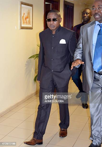 Guinea's former military ruler Captain Moussa Dadis Camara arrives to hold a press conference on May 11 2015 from his exile place in Ouagadougou to...