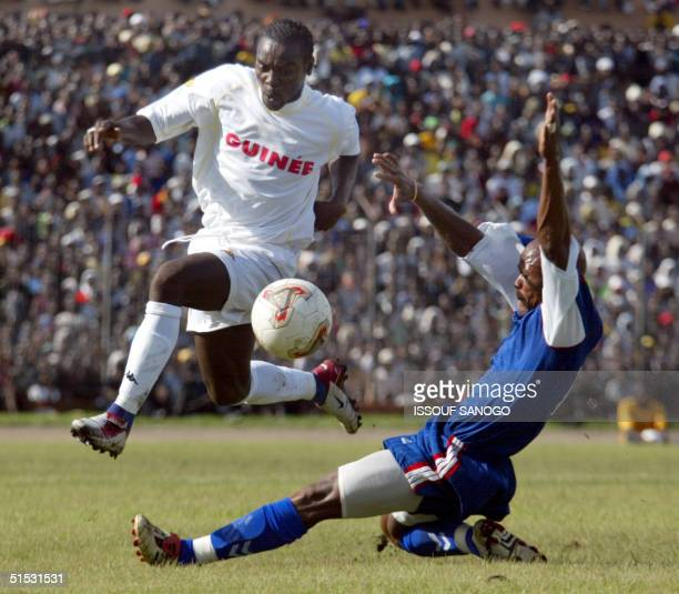 Guinea's forward Pascal Feindouno is tackled by Liberian Tondo Georges 08 September 2002 in Conakry during their African Nations Cup qualifying game...