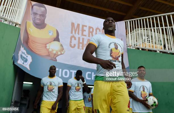 Guinea's National football team players enter the stadium under a poster of late football player Cheick Tiote at the stade de la paix in Bouake on...