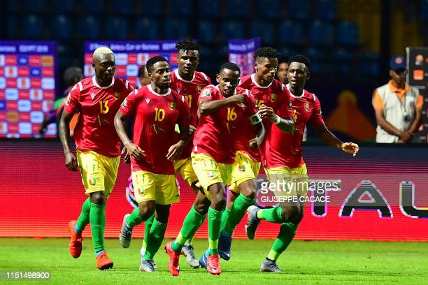 Guinea's players celebrate their equalising goal during the 2019 Africa Cup of Nations football match between Guinea and Madagascar at Alexandria...