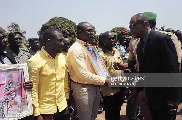 Guinea's President Alpha Conde and Guinea's Chief of staff General Namory Traore speak with family members of UN peacekeepers killed in an Islamist...