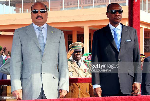 Guinea's President Alpha Conde and Mauritania's President Mohamed Ould Abdel Aziz stand prior to an Organisation for the Development of the Senegal...
