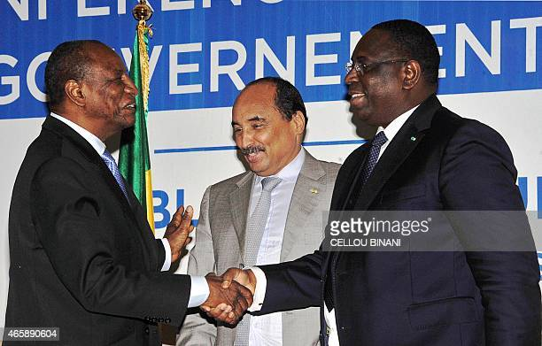 Guinea's President Alpha Conde shakes hands with Senegal's President Macky Sall flanked by Mauritania's President Mohamed Ould Abdel Aziz during an...