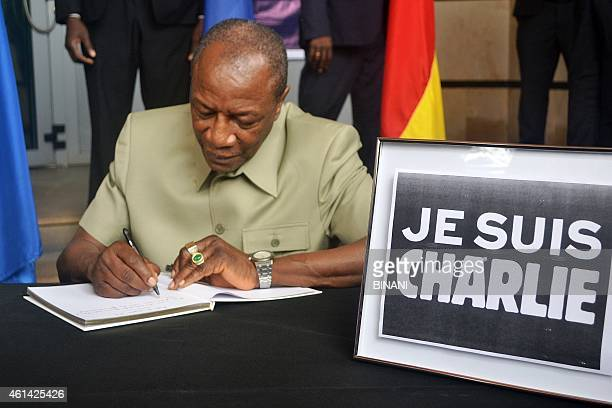 Guinea's President Alpha Conde signs a condolences book at the French embassy in Conakry on January 11 2015 in homage to the 17 victims of the...
