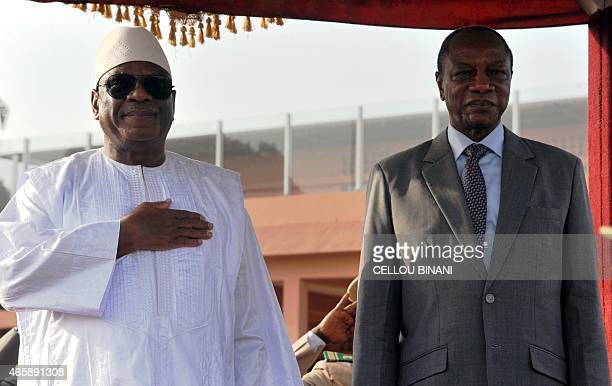 Guinea's president Alpha Conde stands next to Malia's president Ibrahim Boubacar Keita on March 11 2015 in Conakry's airport prior the summit for the...