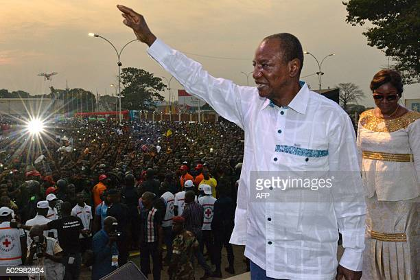 Guinea's president Alpha Konde waves upon his arrival to the Bye bye Au revoir Ebola concert on December 30 2015 in Conakry International artists...