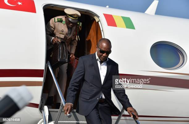 Guinea's President and African Union chairman Alpha Conde gets off the plane as he arrives to attend the 5th African Union European Union summit in...