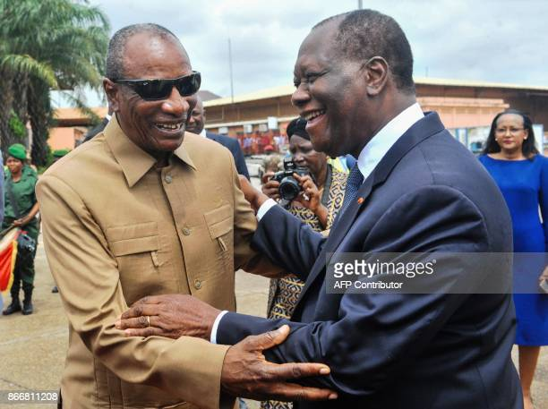 Guinea's President and current chairperson of the African Union Alpha Conde greets Ivory Coast's President Alassane Ouattara upon his arrival at...