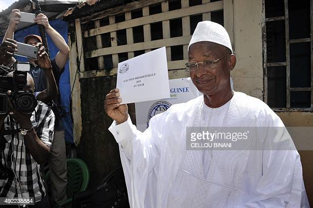 Guinea's presidential candidate and opposition leader Cellou Dalein Diallo poses with his ballot before casting it at a polling station during the...