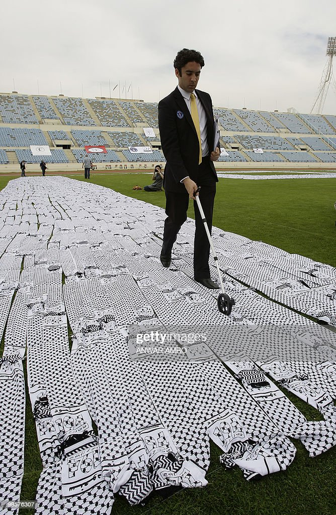 Guiness World Records representative Jack Brockbank measures the length of the world's largest keffiyeh, the traditional black-and-white chequerred Arab headdress, during an event in Beirut on May 15, 2010 to mark the 62nd anniversary of the Nakba or 'catastrophe' of Israel's creation in 1948. The 6,552-metre (21,496 feet) chain of scarves was laid out on the grounds of the Lebanese capital's Sport City Stadium by more than 100 volunteers to form the number 194, signifying the 1948 United Nations resolution that grants Palestinians the right to return to their homes in Israeli-occupied land. More than 760,000 Palestinians -- estimated today to number 4.7 million with their descendants -- were pushed into exile or driven out of their homes in the conflict that followed Israel's creation 62 years ago. PHOTO