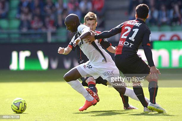 Guingamp' midfielder Younousse Sankhare vies with Rennes' defender Benjamin Andre and Renne's Brasilian midfileder Pedro Henrique during the French...
