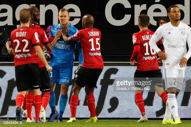 Guingamp's Danish goalkeeper KarlJohan Johnsson is congratulated by his teamates after stopping a penalty kick of Strasbourg's French defender Kenny...