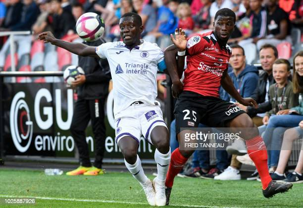 Guingamp's French defender Cheik Traore vies with Toulouse's Ivorian forward MaxAlain Gradel during the French L1 football match between Guingamp and...