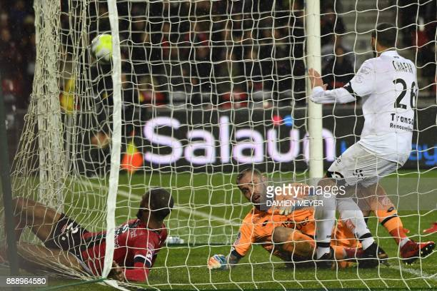 Guingamp's French defender Marcus Coco slips into the cage past Dijon's French goalkeeper Baptiste Reynet as he scores a goal during the French L1...