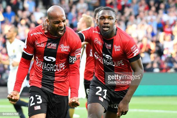 Guingamp's French forward Jimmy Briand celebrates with teammate French forward Marcus Thuram after scoring a goal during the French L1 football match...
