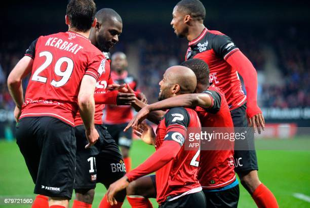 Guingamp's French forward Jimmy Briand is congratulated by his teammates after scoring a goal during the French Ligue 1 football match between...