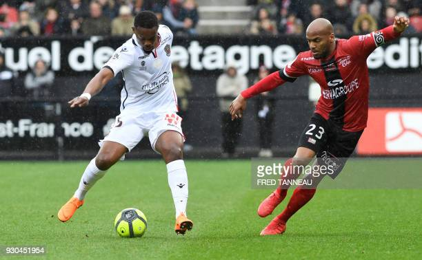 Guingamp's French forward Jimmy Briand vies for the ball against Nice's French midfielder Wylan Cyprien during the French L1 football match Guingamp...