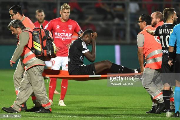 Guingamp's French forward Marcus Thuram is evacuated on a stretcher during the French L1 football match between Nîmes and Guingamp, on september 26,...